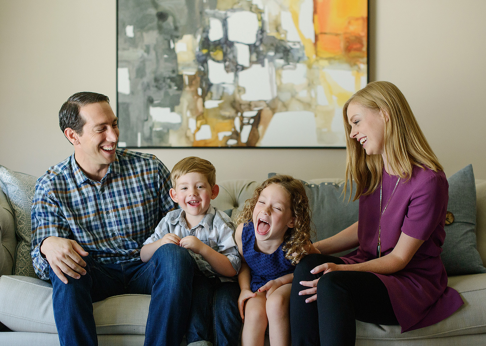 Laughing family photo on the couch lifestyle session against abstract art