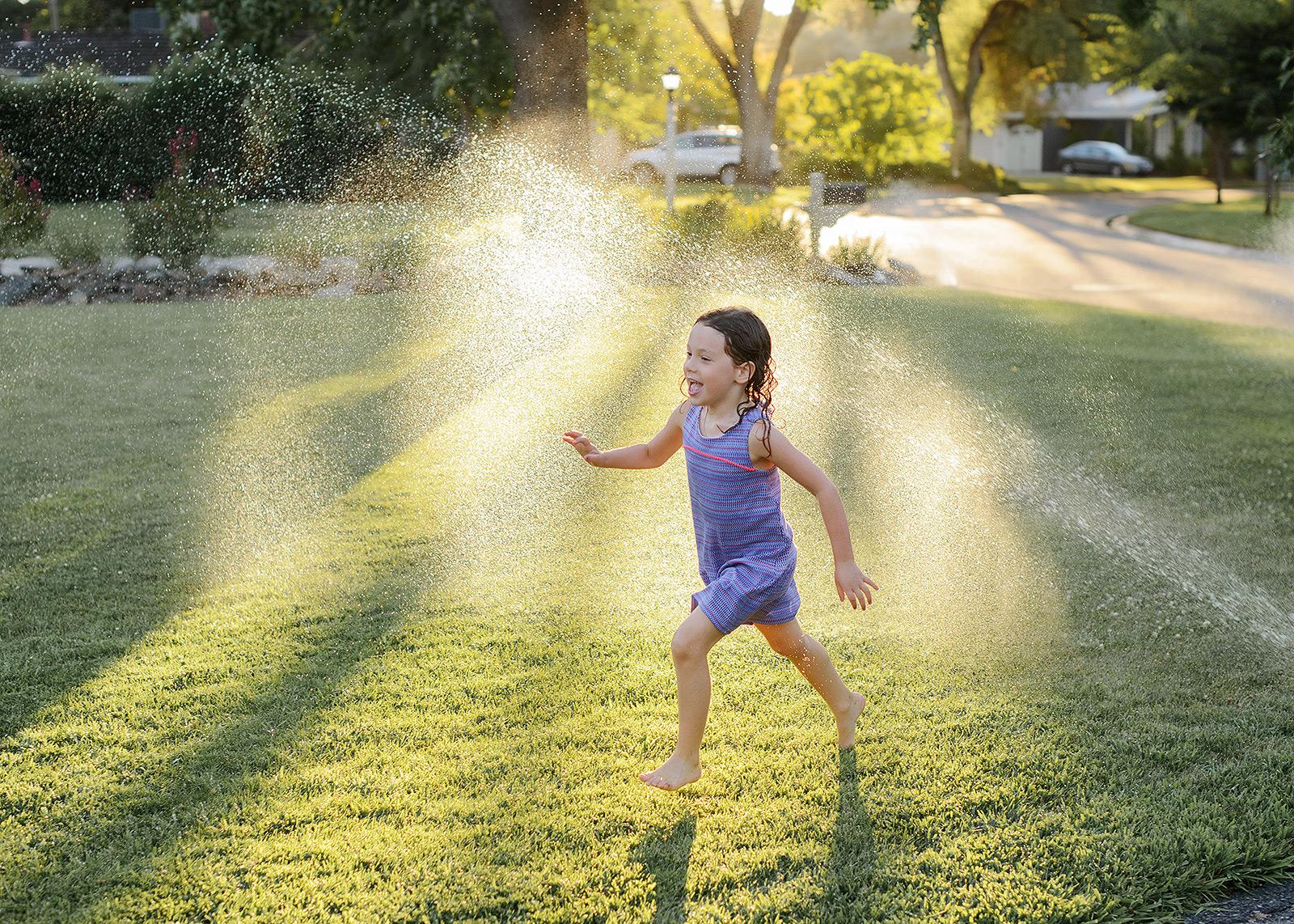 Little girl running through sprinklers on the grass in Sacramento backyard