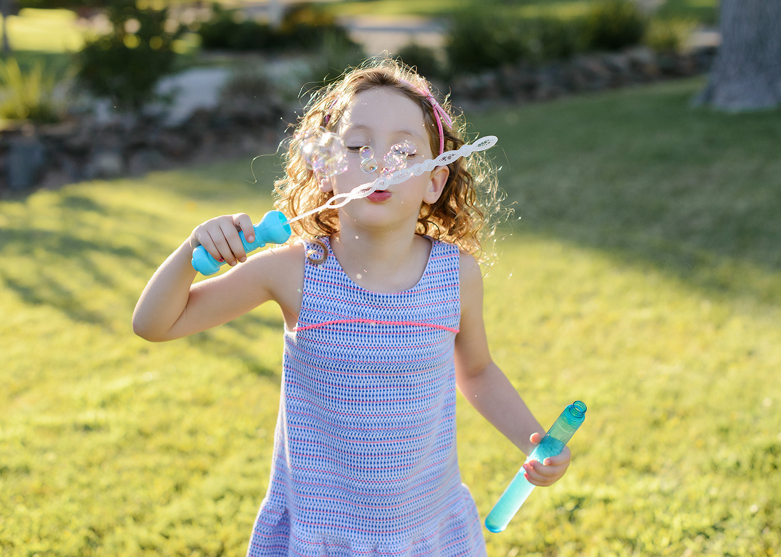 Little girl blowing bubbles in yard outdoors with bubble wand