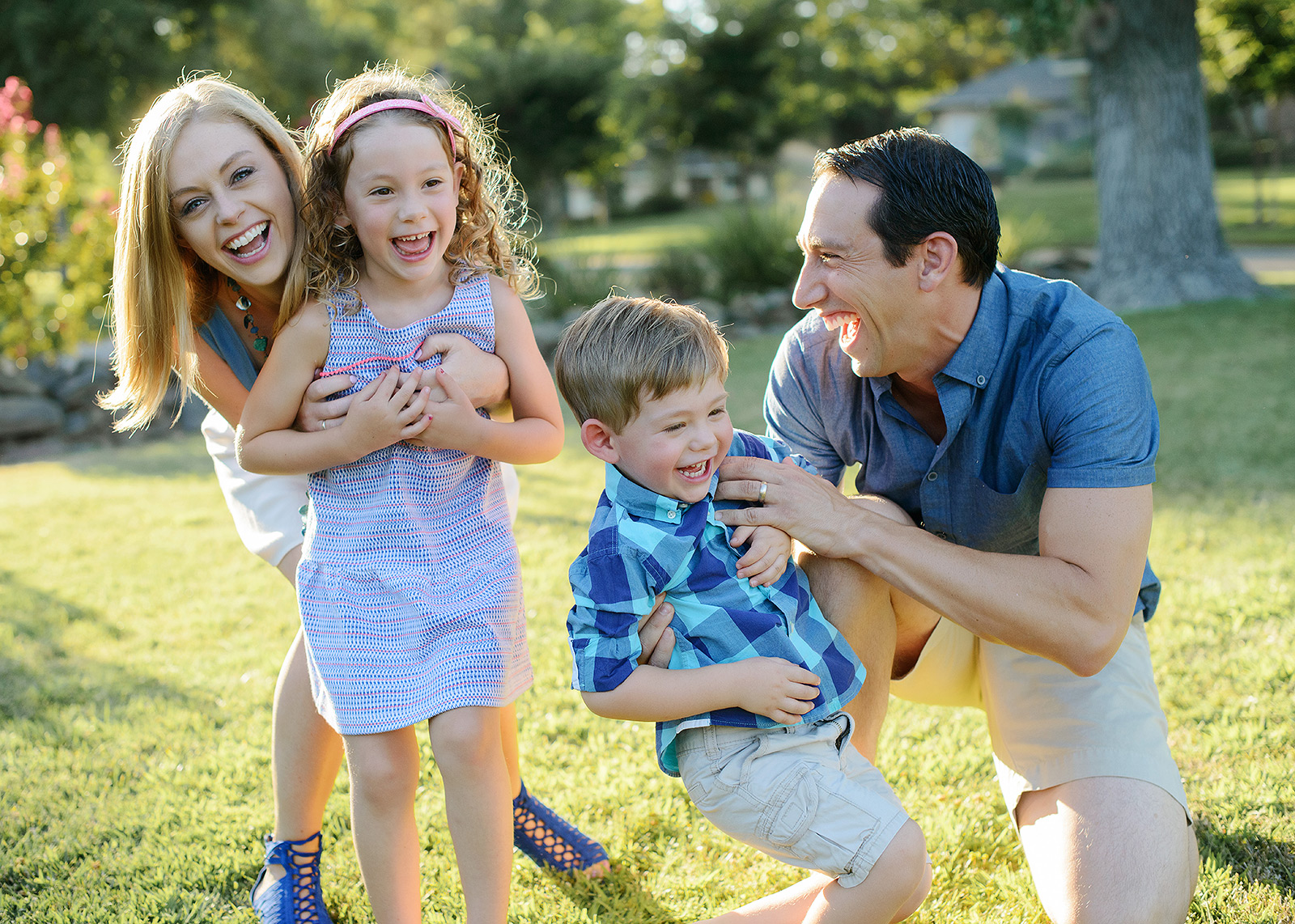 Laughing family photo on the grass outdoors in Sacramento