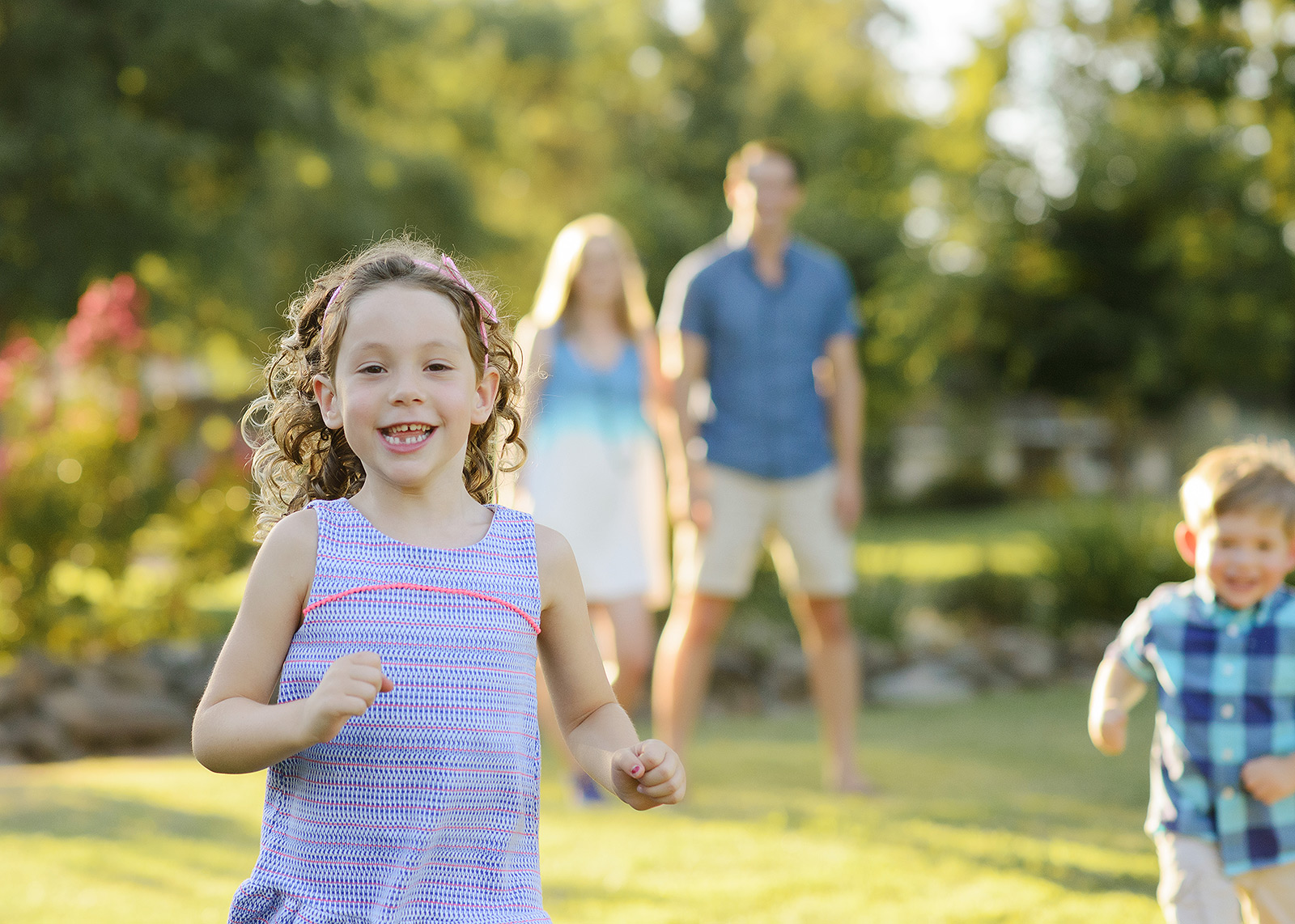 Little girl running in foreground with parents in background in backyard
