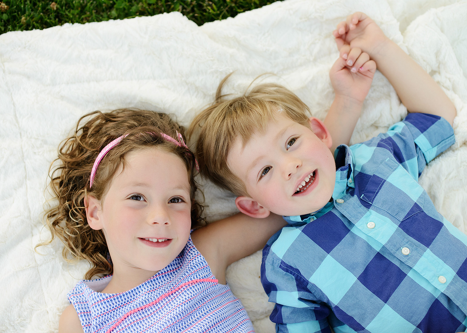 Sister and brother lying on picnic blanket outdoors in Sacramento backyard