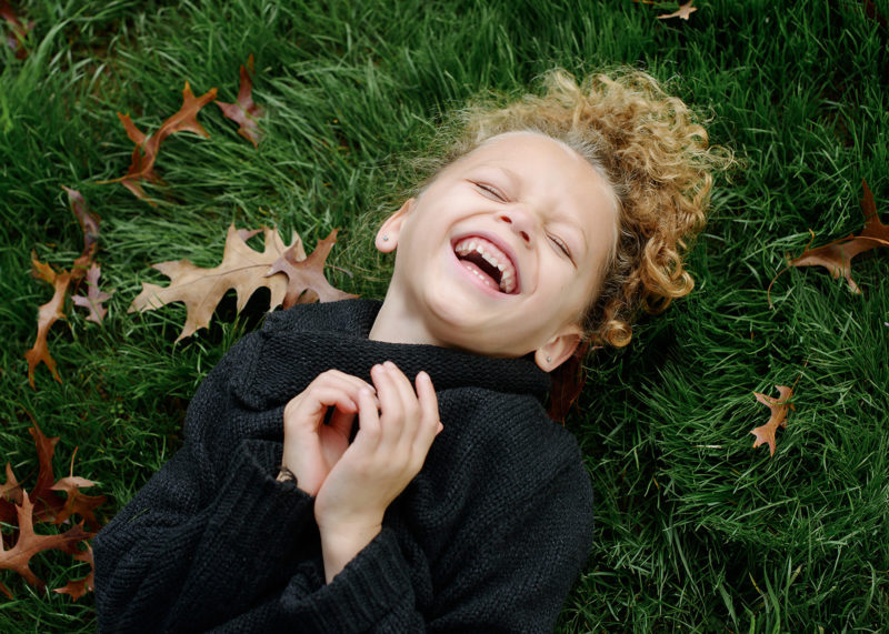 Daughter with blonde curly hair laughing on grass and autumn leaves