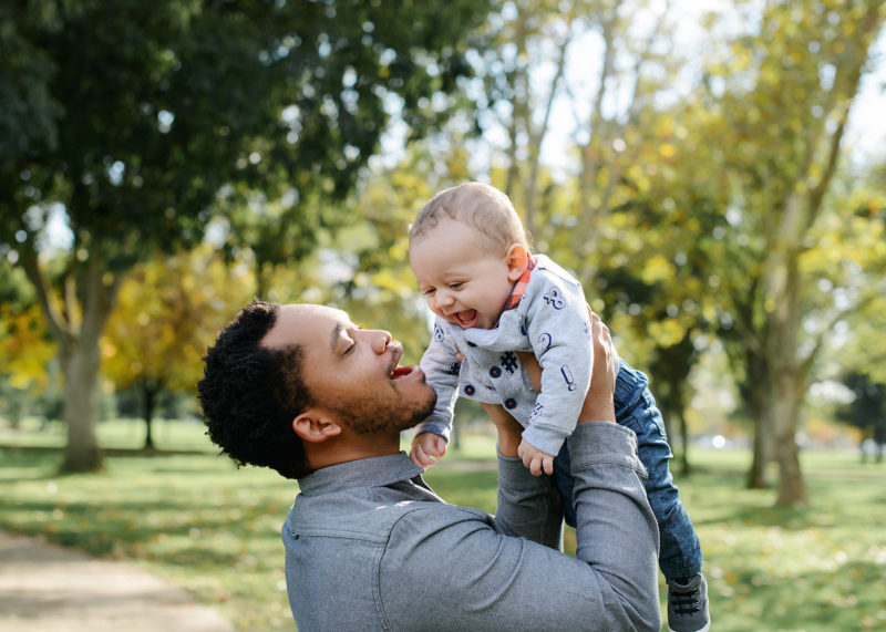 Dad smiling and lifting up baby boy in Sacramento outdoors