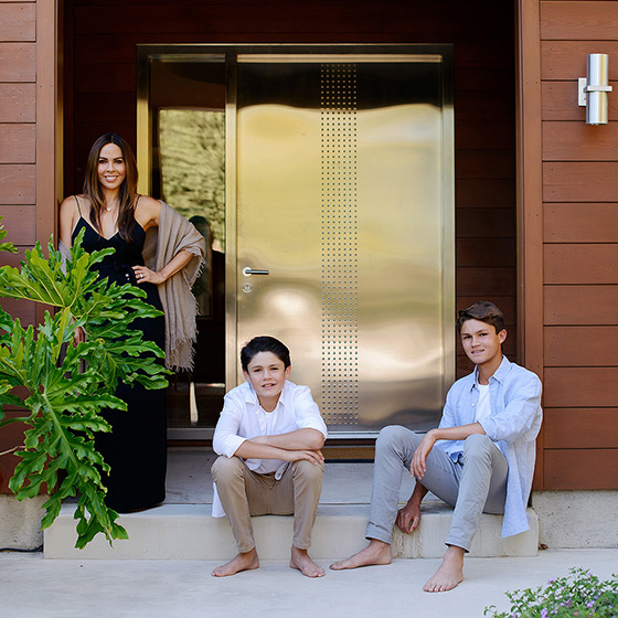 Mom and her sons in front of steel door of Sacramento home