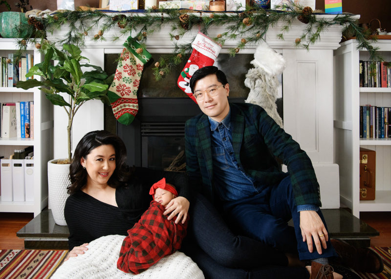 Newborn baby girl in plaid with new parents in front of fireplace and holiday stockings