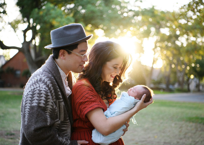 Asian couple with newborn baby girl holding and watching her lovingly in Oak Park Sacramento