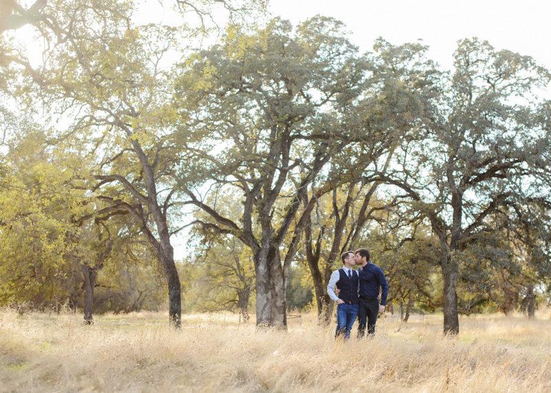 Same sex couple kissing underneath oak trees in golden grass in Roseville