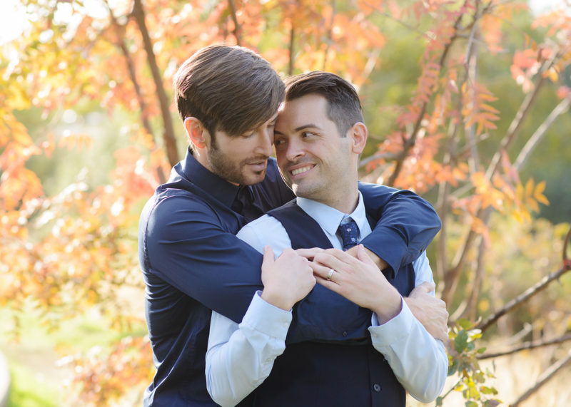 Same sex couple in a loving embrace with orange autumn leaves in background in Roseville