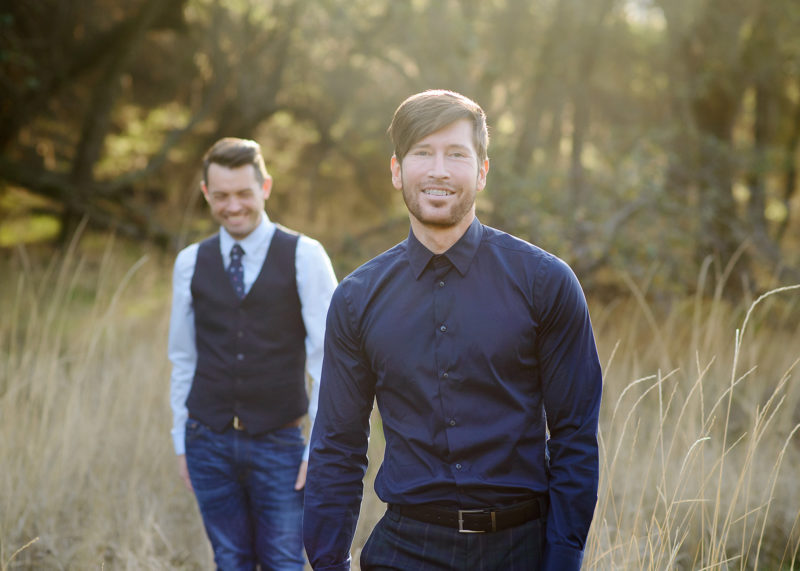LGBT couple posing and smiling for engagement photos during golden hour in dry grass in Roseville