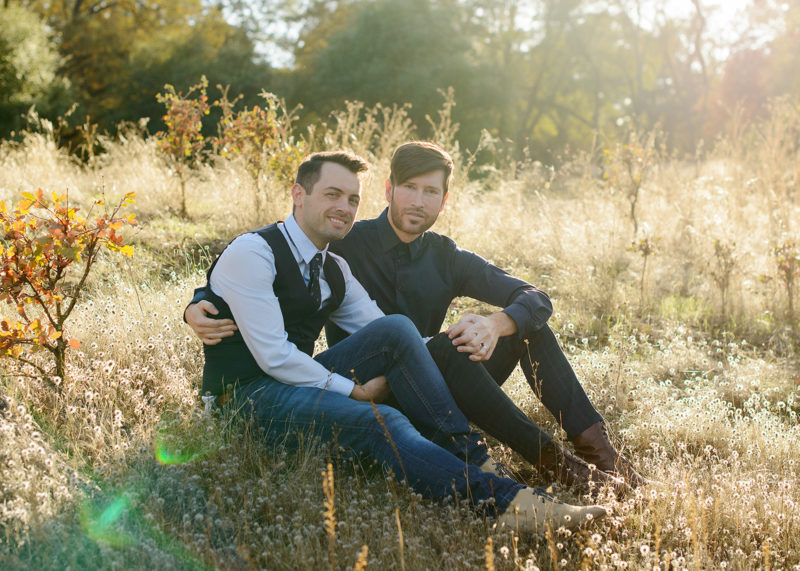 Gay male couple sitting in an embrace on golden grass in Roseville