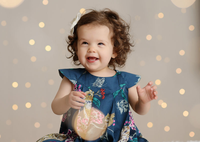 Toddler girl smiling with twinkle light background and bokeh effect