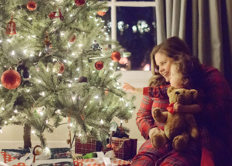 Mother and daughter in matching pajamas putting on Christmas tree ornaments
