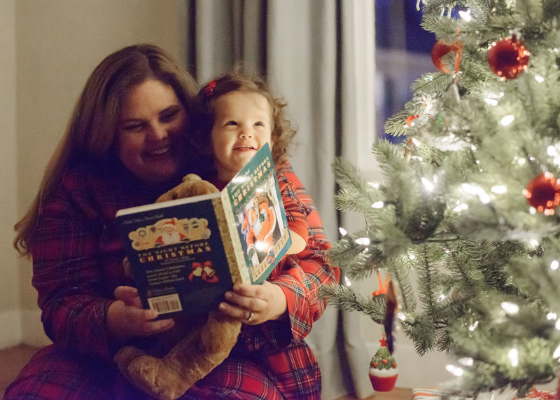 Mom reading The Night Before Christmas book to daughter by Christmas tree
