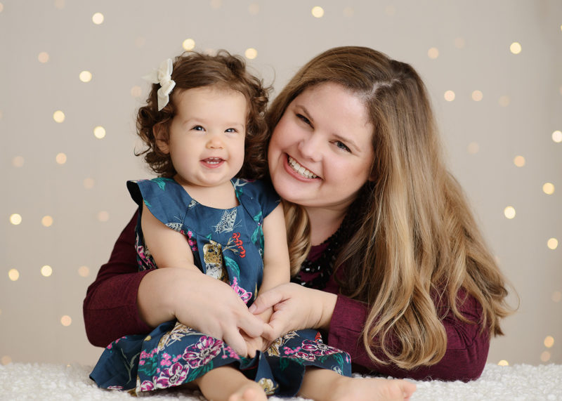 Mom and daughter smiling in studio with twinkle bokeh lights background