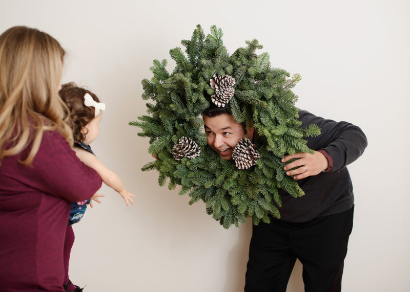 Dad making funny faces with holiday wreath in studio