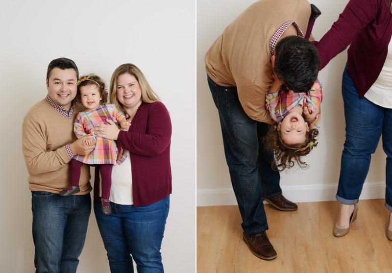 Dad holding toddler daughter upside down laughing in studio
