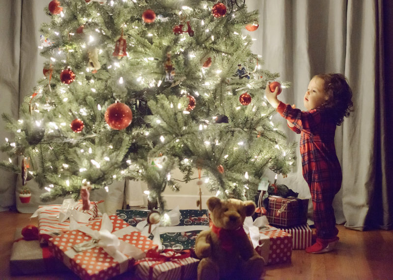 Toddler girl in pajamas reaching for Christmas tree ornament with teddy bear in foreground