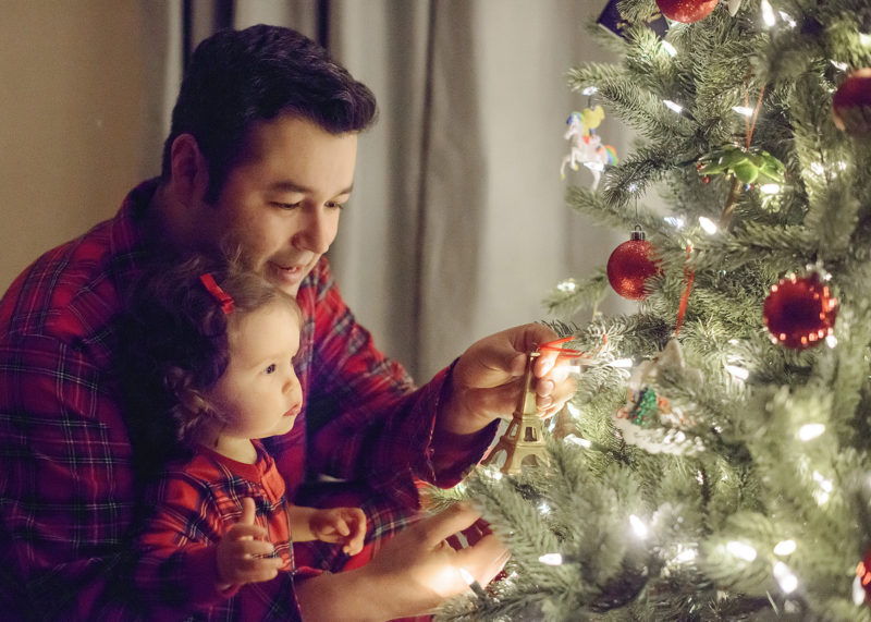 Father and daughter in matching pajamas putting ornaments on Christmas tree