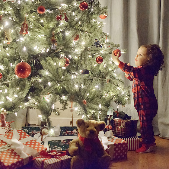 Toddler girl in pajamas reaching for Christmas tree ornament