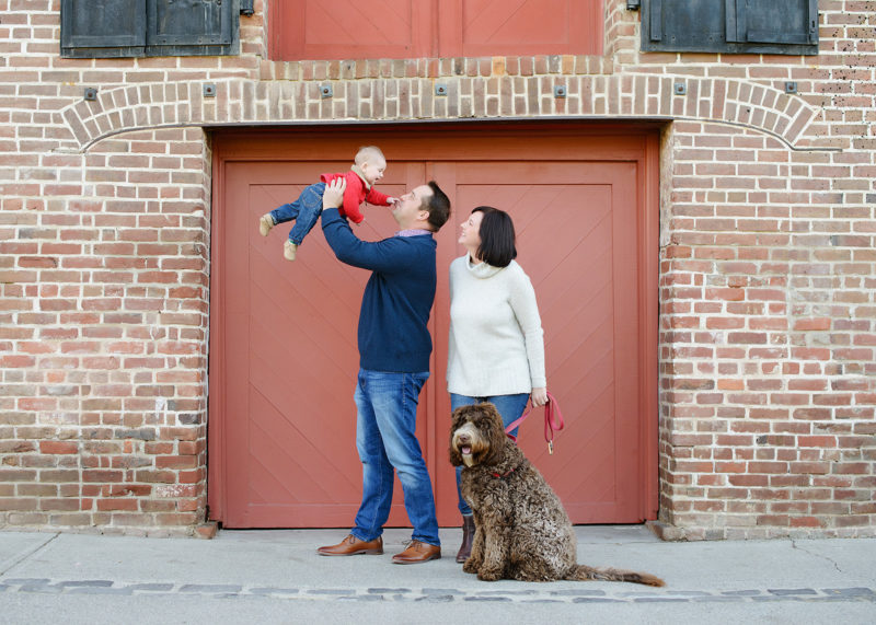 Dad holding baby boy up in the air while mom and dog watch in front of red brick background Old Sacramento