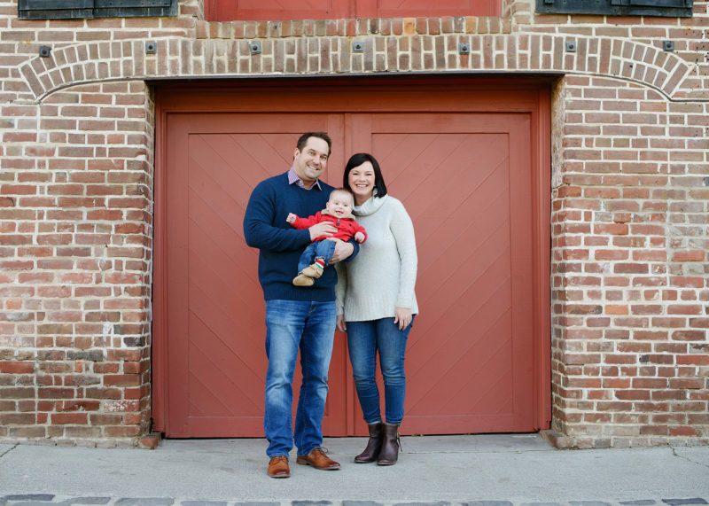 Mom and dad holding baby boy in front of red brick background in Old Sacramento