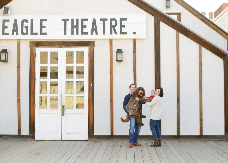 Family with dog posing in front of Eagle Theatre in Old Sacramento