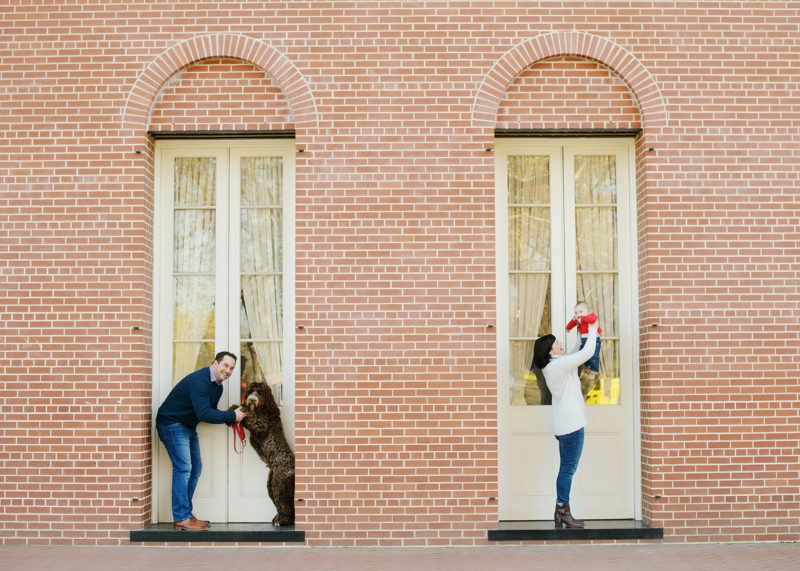 Dad and dog and mom and baby pose in front of doors and red brick in Old Sacramento
