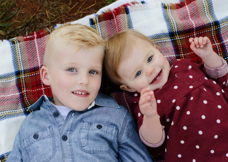 Big brother and little sister cuddling on flannel blanket and looking at camera in Apple Hill