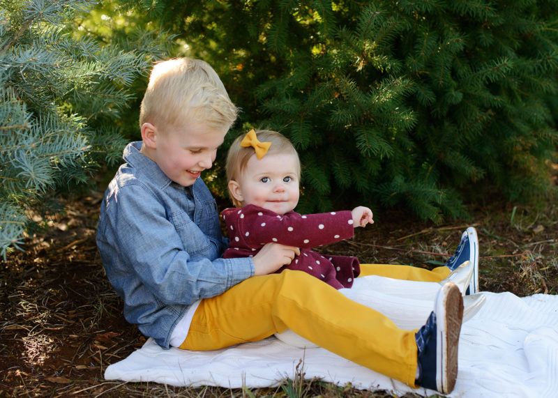 Big brother and little sister cuddling on blanket by pine trees in Apple Hill
