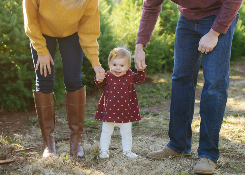 Baby girl standing up while parents hold her hand outdoors in Apple Hill