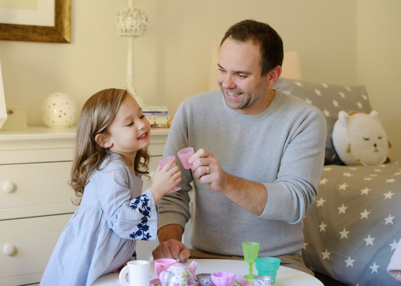 Dad and daughter having a tea party in her room