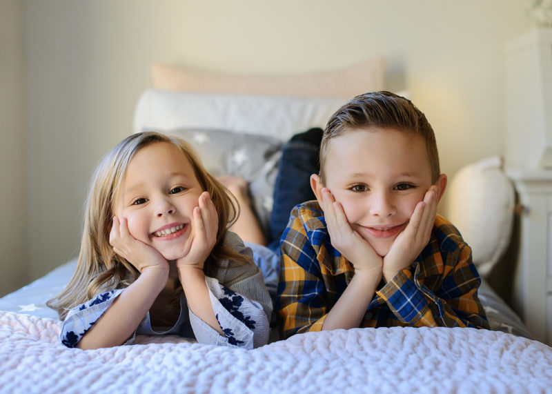 Sister and brother on bed smiling at camera in Sacramento