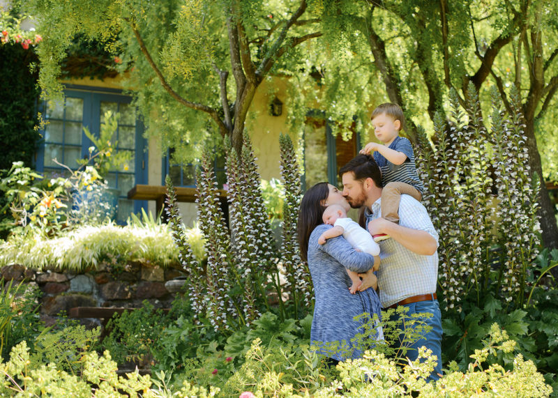 Parents kiss as they hold sons in front lawn greenery Sacramento