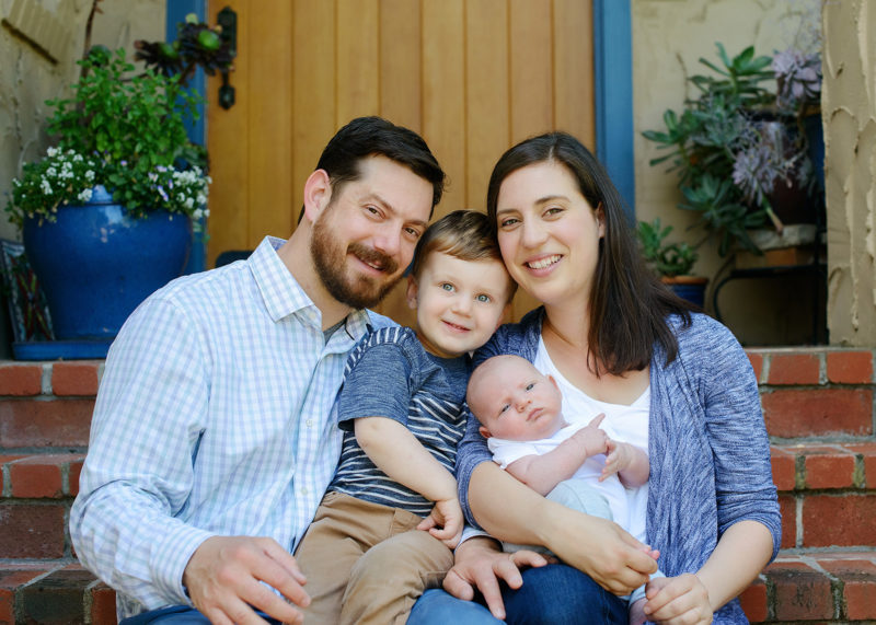 Lifestyle family portrait while sitting on porch steps in Sacramento home