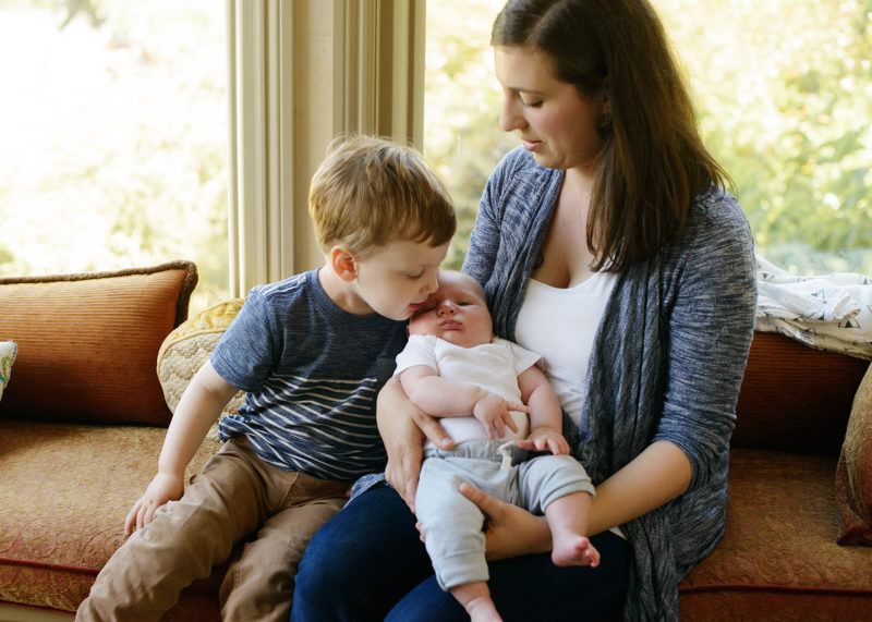 Big brother kissing baby brother while mom holds him lifestyle photos in Sacramento