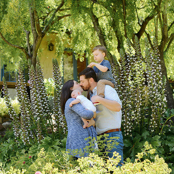 Parents kissing while holding babies in front of family home and garden in Sacramento