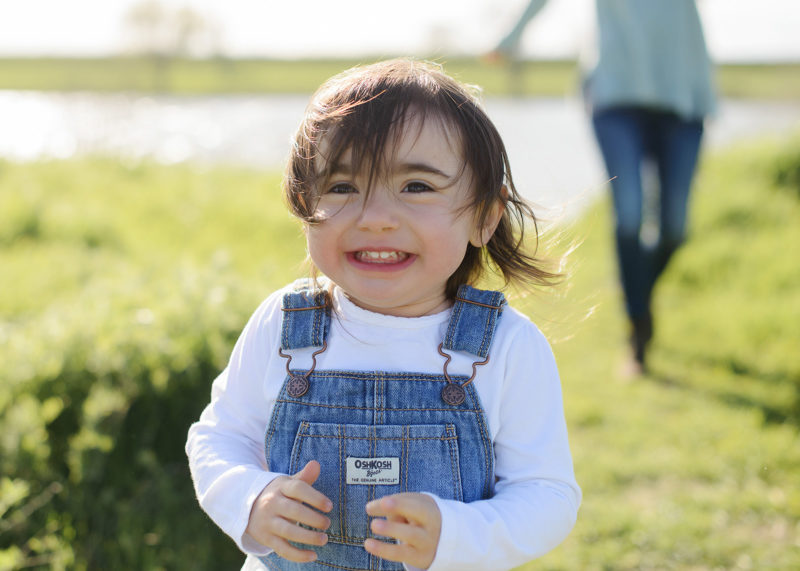 Toddler girl wearing coveralls smiling in field of wildflowers in West Sacramento