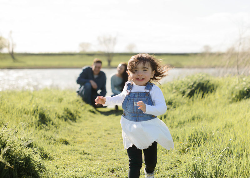 Toddler girl running in grassy field in West Sacramento