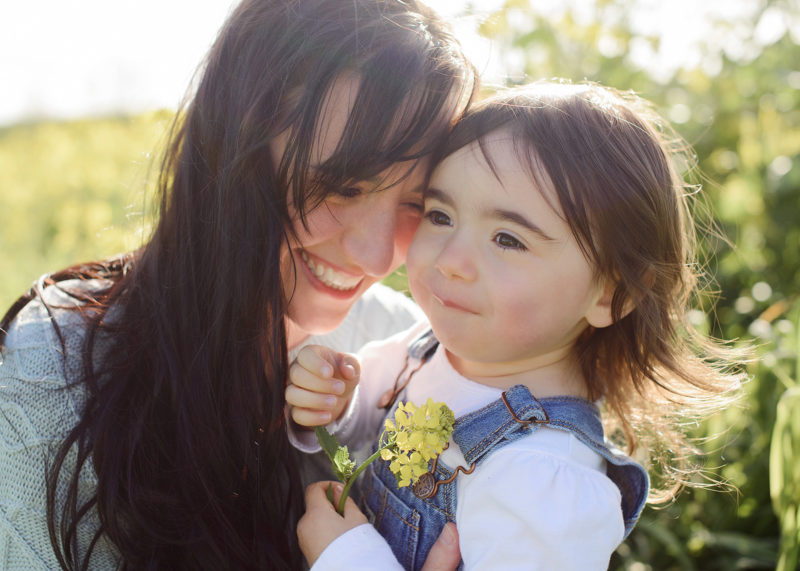 Mom lovingly smiling at toddler daughter in natural light