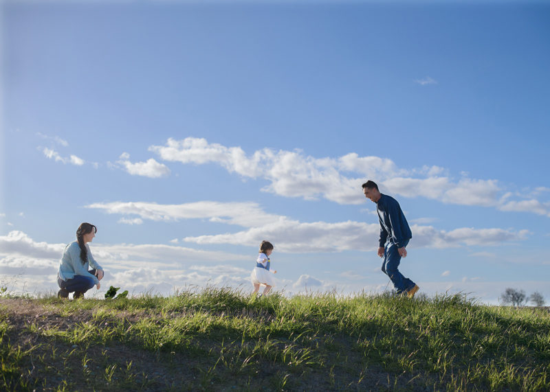 Toddler running towards dad in grassy field with blue sky and clouds