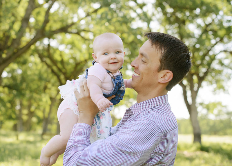 Dad smiling as he lifts baby girl in the air in Fair Oaks park