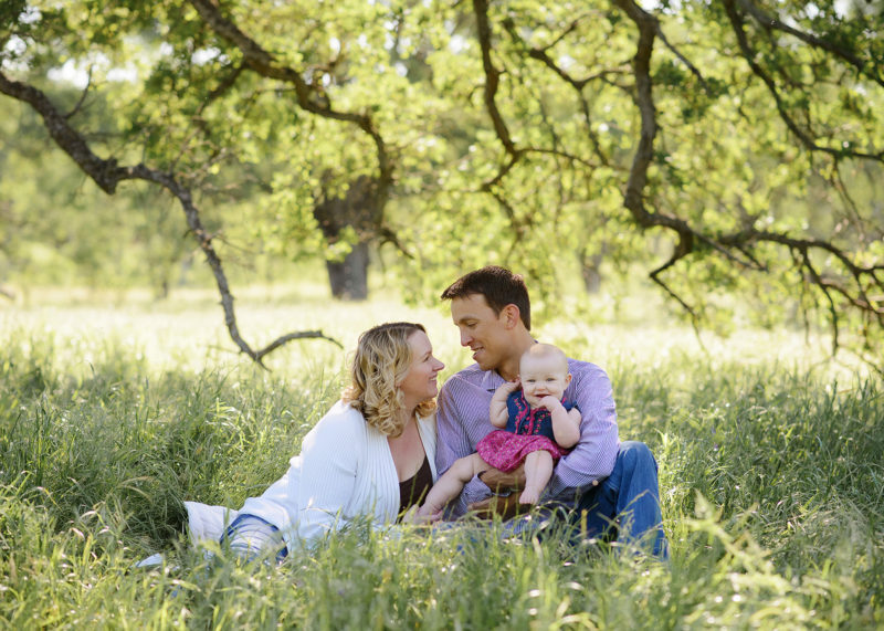 Mom and dad holding baby girl while sitting on grass underneath the tree in Fair Oaks Park