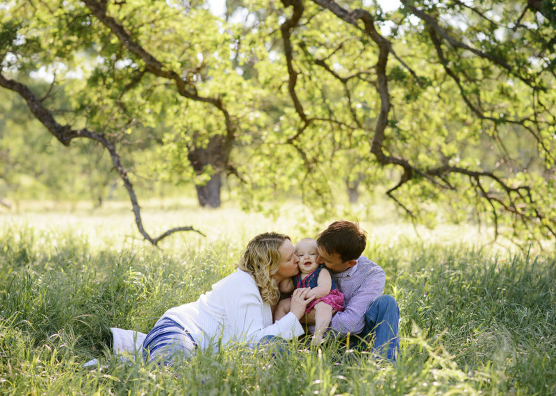 Mom and dad kissing baby girl while sitting on grass underneath the tree in Fair Oaks Park