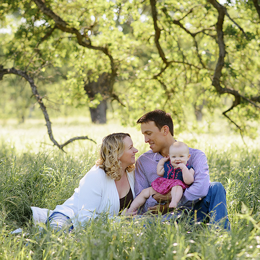 Family portrait with smiling baby girl sitting in grass under a tree in Fair Oaks