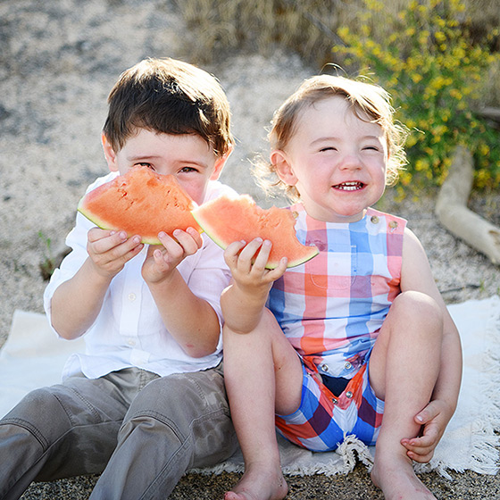 Brothers smiling and eating watermelon on beach sitting on sand in Folsom Lake