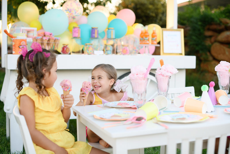 Little girl with ice cream on her nose laughing at party table