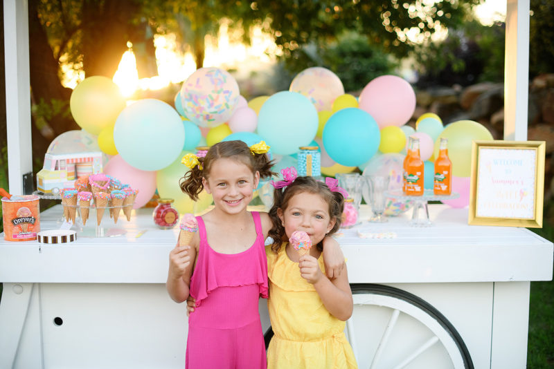 Little girls eating icecream in front of dessert display birthday party