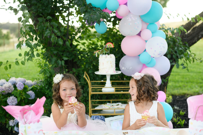 Little girl eating a cupcake with balloon arch and unicorn cake in backdrop