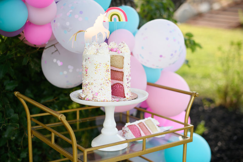 Three layer pink cake with unicorn and rainbow topper detail
